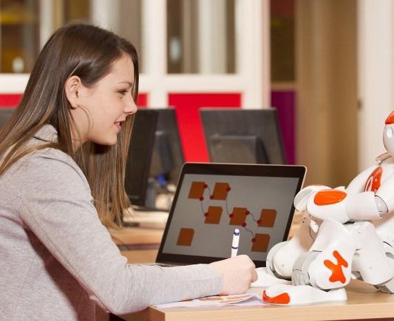 una estudiante trabajando la progrmacion de un robot - robótica