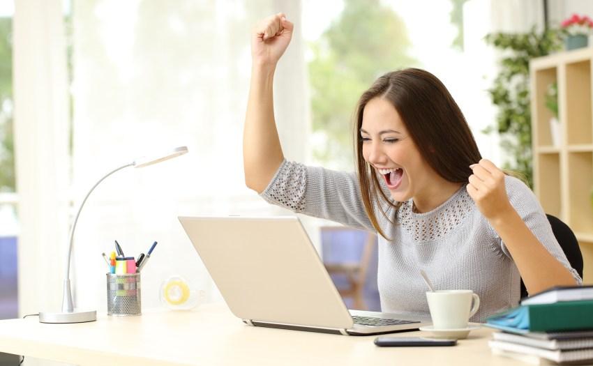 mujer sentada frente a una laptop celebrando - 3 estrategias educativas