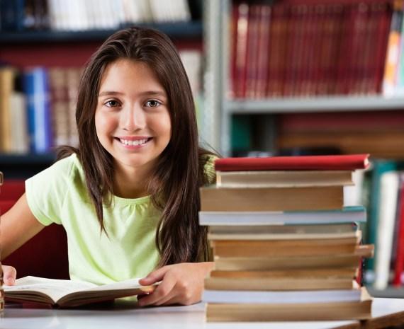 Estudiante con libros sobre la mesa sonriendo - motivación