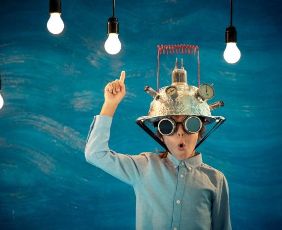 Estudiante con un dedo levantado y con bombillas colgando simulando que tiene una idea - innovación