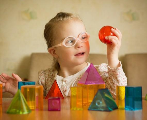 niña con necesidades especiales juega con figuras geometricas de colores - educación especial