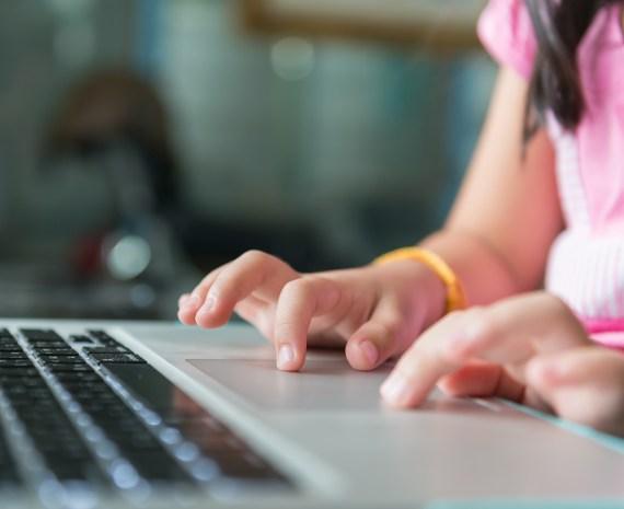 manos de una niña aobre un teclado - keyboarding