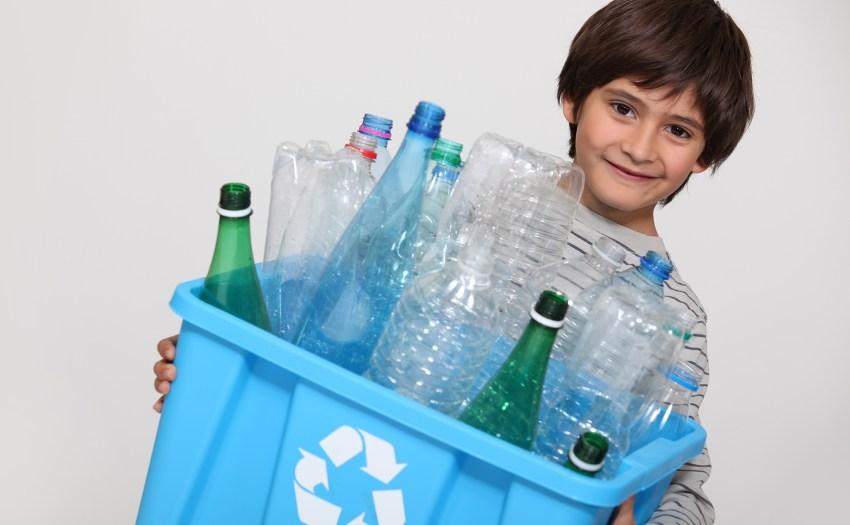 Niño sujetando cajón con matriales reciclabes y desperdicios sólidos