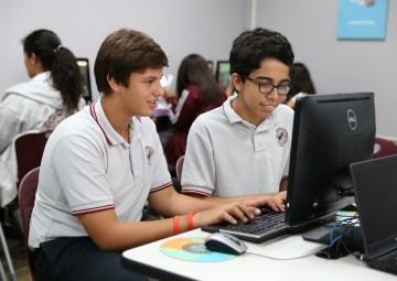 Dos estudiantes frente a una computadora practicando typing