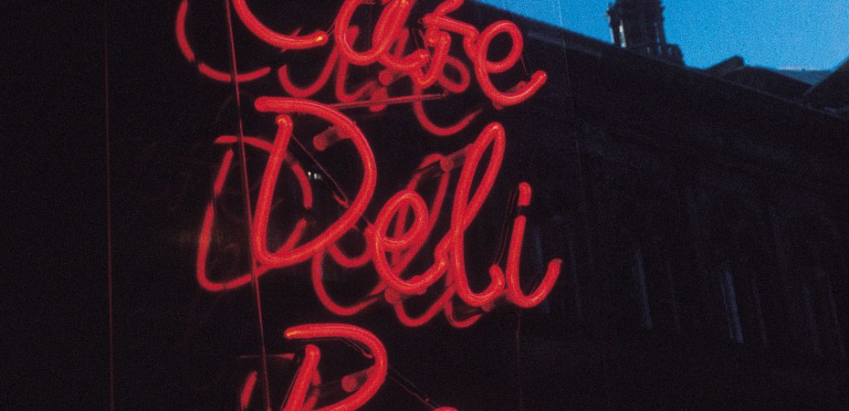 "shop window with ""cafe, deli, bar"" in red fluorescent light"