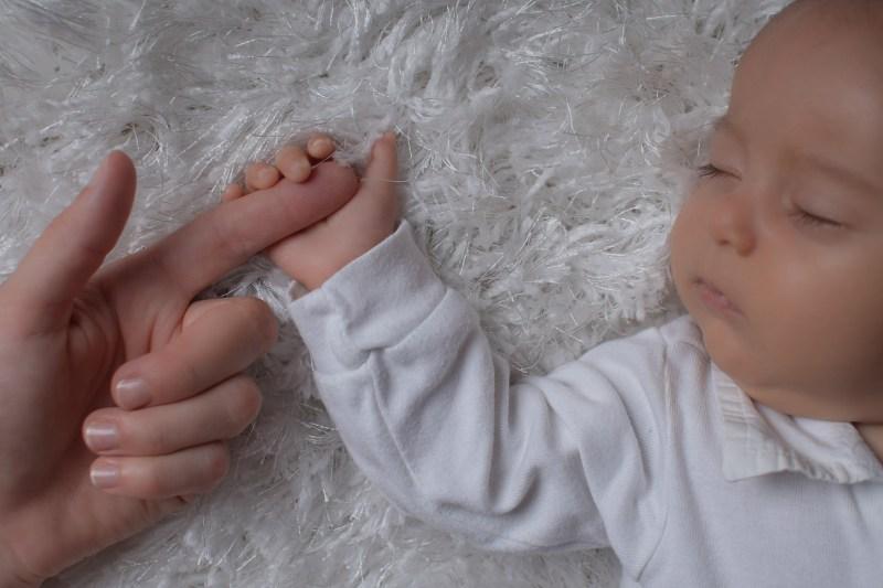 Babyfoto vom Fotograf im Mostviertel, Baby hält Finger von Mama und zeigt schläft