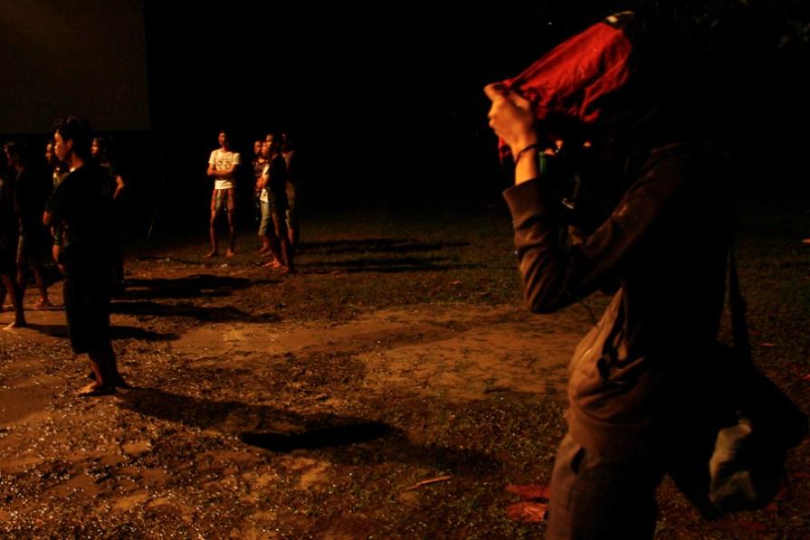 ardi wilda memotret panggung dare 2 care di PPSJ, kondisi hujan dia mau tak mau memotret sambil menggunakan parasut tas kameranya untuk melindungi kameranya