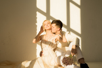 Bride and groom sitting on the floor and hugging