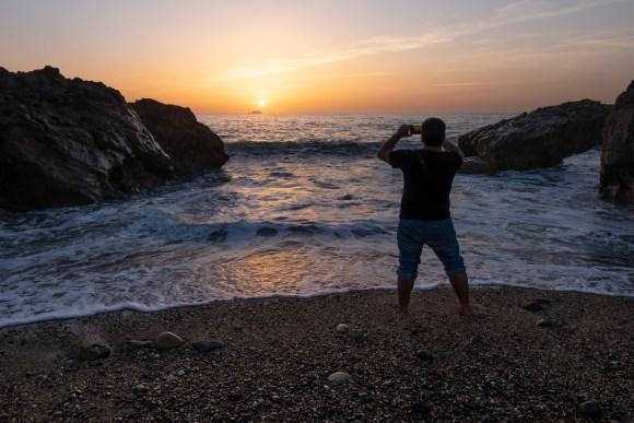 Chico hace fotografia en puesta de sol en playa de Oporto.