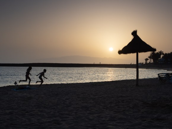 niños corriendo en la playa durante la puesta de sol en playa de Tenerife