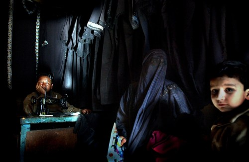 """A Muslim Kashmiri woman sits inside a shop with her children where traditional Islamic veils are made, March 26, 2002 in Srinagar, the summer capital of Indian held Kashmir. The shadowy group, Lashkar-e-Jabbar, also known as Allah's Army sent a letter to a local newspaper saying that Muslim Kashmiri women must adhere to the dress code or face acid attacks beginning on April 1, 2002. The leader of the group also wrote, """"if our members see any boy or girl or any illegal couple doing acts of immortality they will be killed there and then"""".The same group claimed responisiblity for two acid attacks on women in Srinagar last year. Kashmir has been the center of the ongoing dispute between India and Pakistan since the region was partioned when the British left in 1947.(Ami Vitale/Getty Images)"""