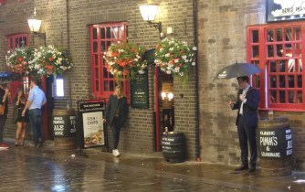standing in the rain in front of a pub