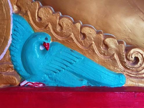 Taube unter einer Buddhastatue, Pagodenfeld in Pindaya, Myanmar