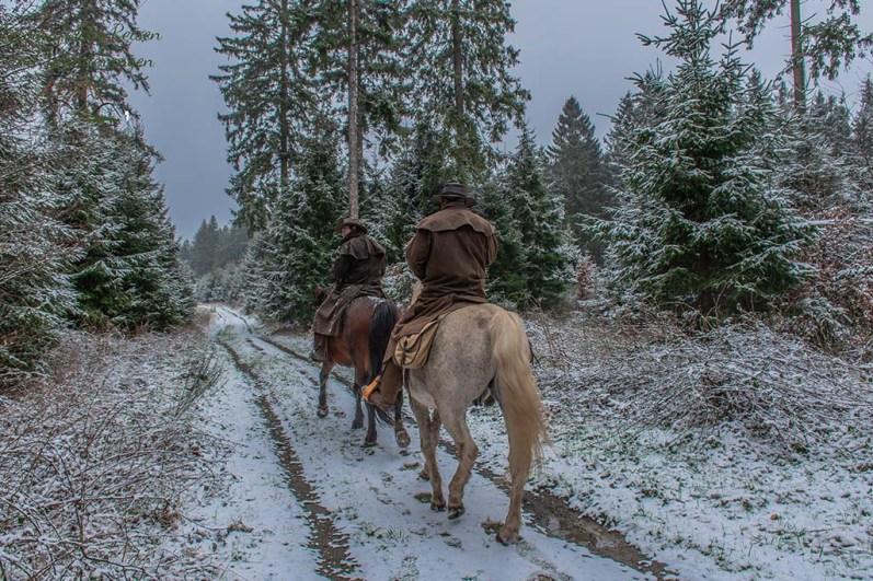 Ross und Reiter von hinten im Schnee