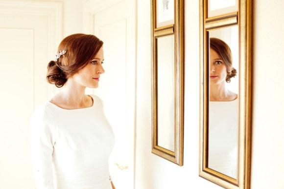 Novia posando delante del espejo antes de salir a la ceremonia