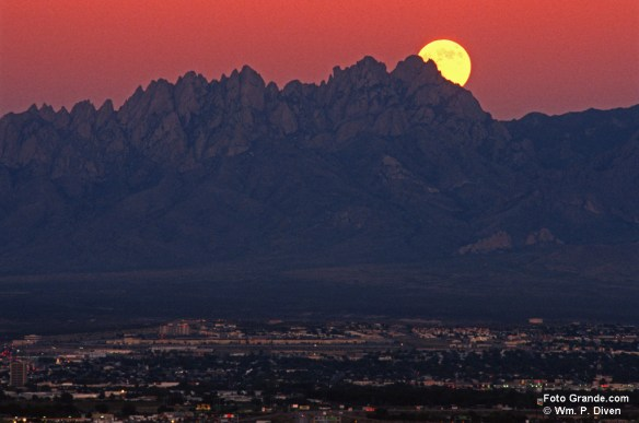 The moon rises at sunset over the Organ Mountains and Las Cruces, N.M. © William P. Diven