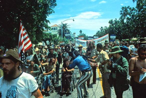 Vietnam veteran Ron Kovic carries flag while leading protest march. Photo by Tony Schweikle, State of Florida Archives, Florida Memory, http://floridamemory.com/items/show/17306.