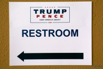 A campaign-branded restroom sign at the Santa Ana Star Center points to relief. © William P. Diven