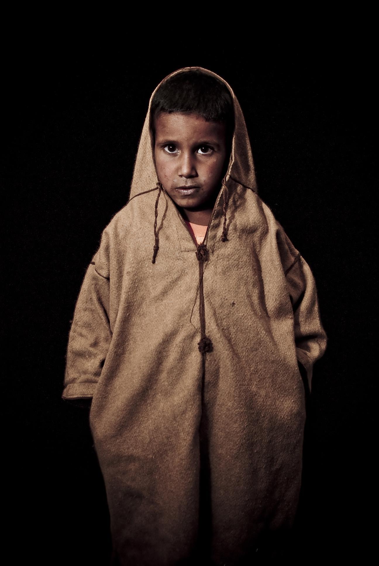 Foto tomada en los campamentos de guerra de Tinduf, en la wilaya de Smara, durante uno de nuestros viajes fotográficos. Estuvimos colaborando con una ONG llamada el Bubisher, que visita los colegios con un bibliobus, fomentando la lectura en español y enseñando a los niños el préstamo de libros (están acostumbrados a que les den cosas, pero no a devolverlas). La luz es simplemente un flash rebotado al techo del bibliobus, y el fondo, la noche del desierto. Ese mismo niño tuvo un pequeño accidente 2 días antes, durante una visita a su colegio, y tuvimos que llevarlo al hospital, donde le tuvieron que amputar la última falange del dedo meñique. En ningún momento soltó una lágrima. A los dos días ya estaba de nuevo revoloteando alegremente alrededor nuestra.