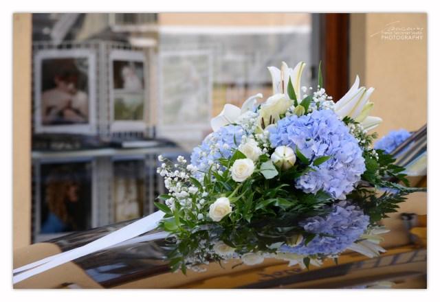 Fotografo Matrimoni. Molta cura per l'allestimento floreale sull'auto degli sposi. Il viaggo non sarà lungo, ma devono essere fissati saldamente. #weddingflowers #allestimentofloreale #fiorisullauto #lamargheritafiori