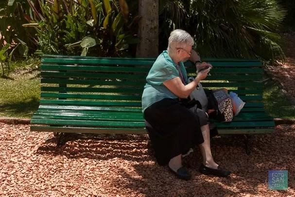 Fotografía de señora sentada en jardín botánico
