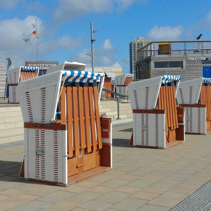 Beautiful white, blue striped beach chairs with brown wooden details.