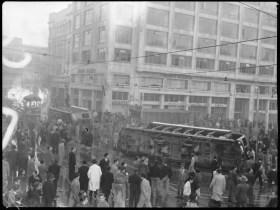 Carrera 7 con avenida Jiménez. Frente al tranvía en llamas el edificio Agustín Nieto, en cuya entrada fue asesinado Gaitán.   Publicada en:  •El 9 de abril: 50 años después. El saqueo de una ilusión. Bogotá: Ediciones Revista Número, 2007. p. 66