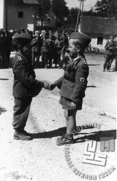 Protikomunistično zborovanje 27. avgusta 1944 v Rovtah ob drugi obletnici delovanja protikomunističnih enot v tem kraju. Odvilo se je res lepo praznovanje s številnimi govorniki, najbolj pa je odmeval govor generala Leona Rupinka, so poročali v časopisu Slovenec 29. avgusta 1944. Dečka se po odraslo rokujeta in prevzemata vlogo, ki jo imajo ponavadi odrasli. Deček na levi, Niko Suvajdžić, vnuk generala Leona Rupnika je bil večkrat nespregledan mali gost protikomunističnih zborovanj po Sloveniji.