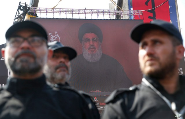 Hezbollah security forces stand guard as their leader Sheik Hassan Nasrallah speaks via a video link on a screen in the southern suburb of Beirut, Lebanon, Sept. 10, 2019.