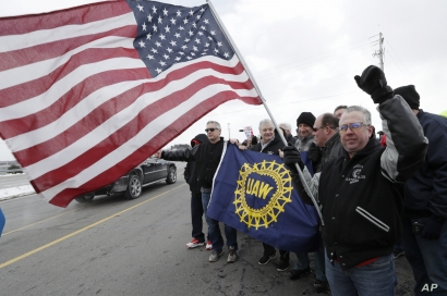 FILE - A General Motors employee holds an American flag as colleagues gather outside the plant, March 6, 2019, in Lordstown, Ohio. The plant was idled.
