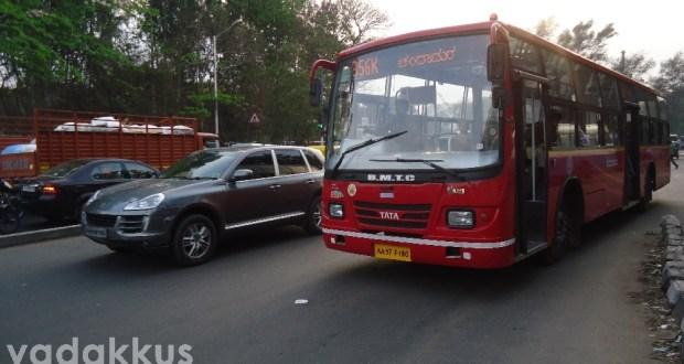 A Porsche Cayenne overtakes BMTC 356K Route Tata bus.