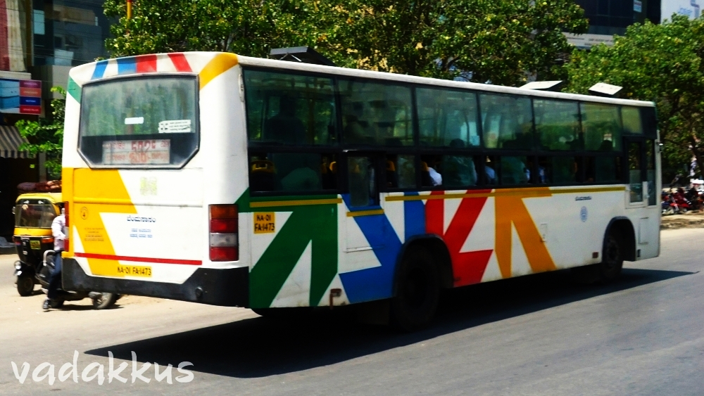 "A BMTC bus with colorful ""arrows"" as livery running on Outer Ring Road"