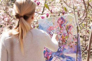 woman in white long sleeve shirt holding white and blue floral painting