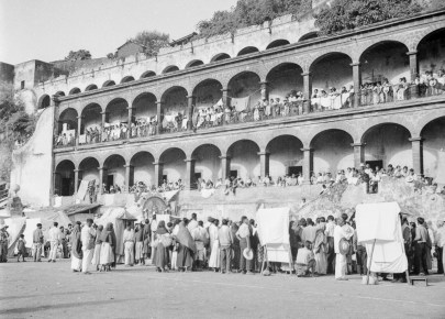 A crowd by an arched building
