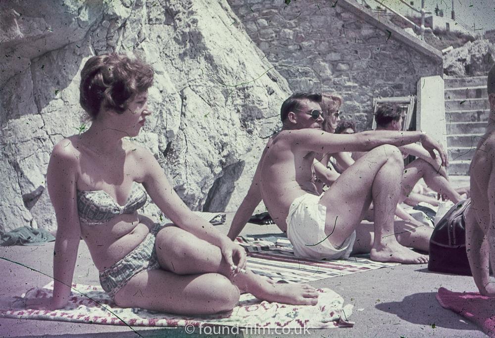 Distracted girl in a bikini on a beach towel