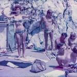 Girl in bikini building muscles on the beach, late 1950s