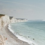 White cliffs and pebble beach with a crane