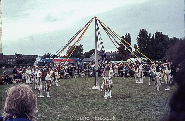 Girls dancing round a may pole