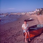 A boy sitting on a dingy on a beach
