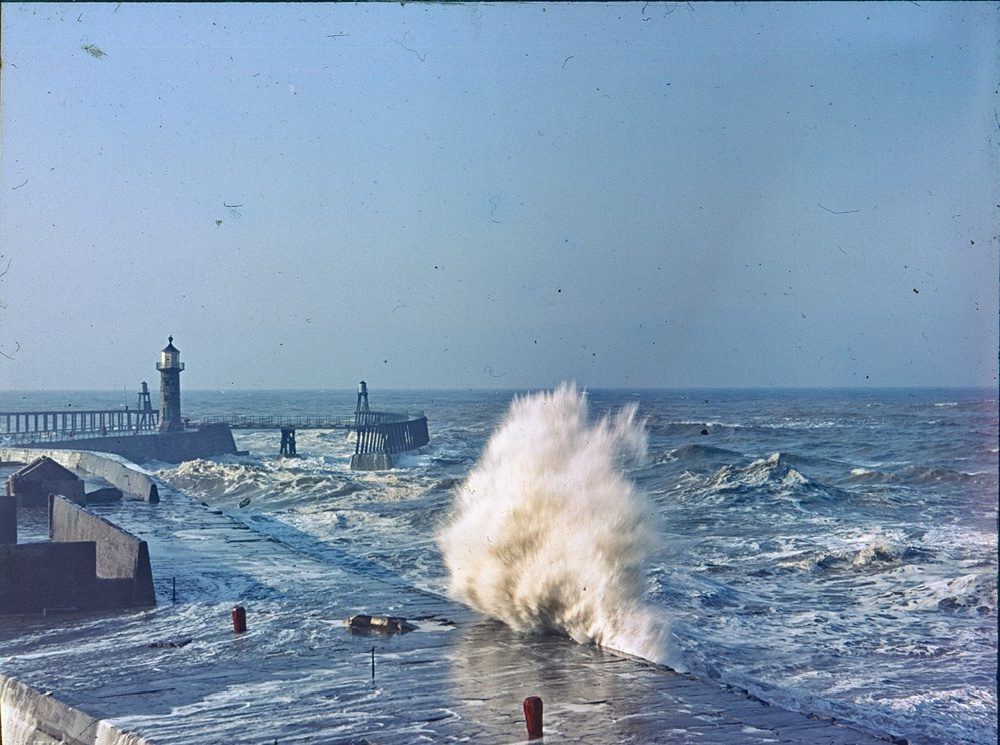 Sea breaking with lighthouse in the distance