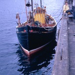 A Kodachrome slide of a fishing boat moored up at the side of the quay in Ullapool in August 1967