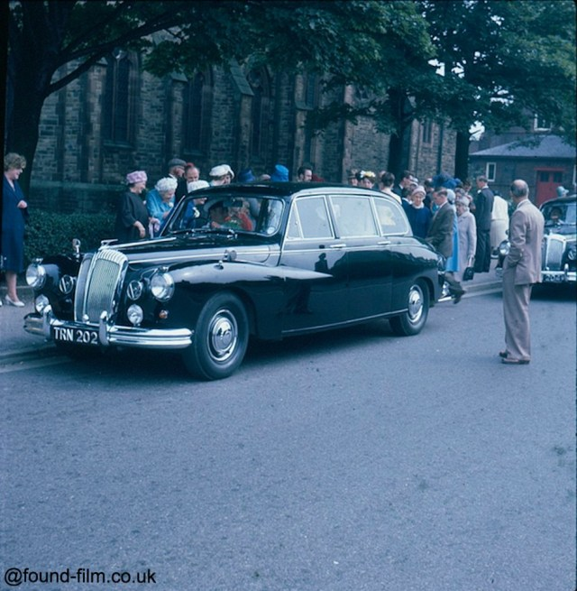 A group of people surrounding a car at a wedding