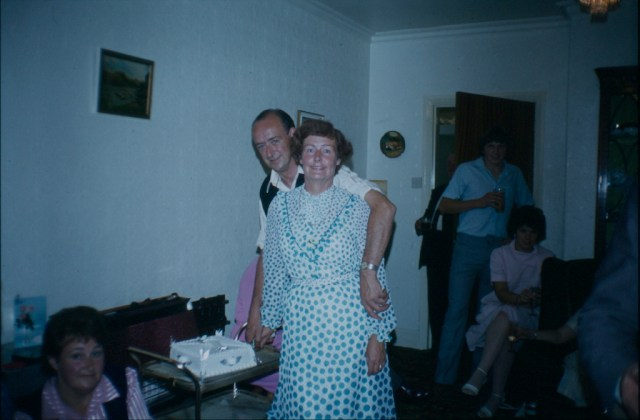 A flash light illuminated photo of a couple taken at a party
