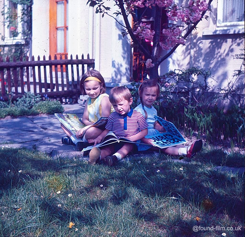 Children sitting with books on a lawn