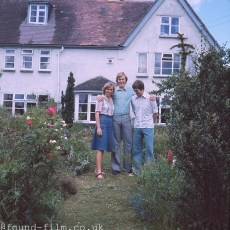 A family group standing in the garden of their cottage