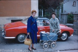Two women and a baby by a red sports car, 1958