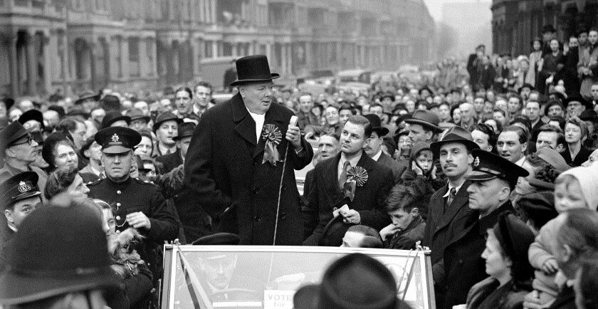 Sir Winston Churchill speaking at Blythe Road, Hammersmith, London, when he made an eve of poll tour to address the crowds on behalf of the Conservatives. Seated in the car is the Conservative candidate Mr A. Fell. Mr Churchill addressed four meetings.