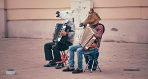 Two people with horse masks playing instruments.