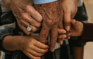 Younger hands holding an older hand
