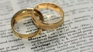 two wedding bands on top of a dictionary page